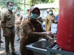 Bupati Mundjidah Wahab mencoba langsung alat cuci tangan yang diserahkan di Pasar Pon Jombang, Senin pagi (13/04)